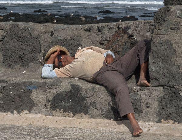 Siesta. Alter schlafender Mann am Hafen.