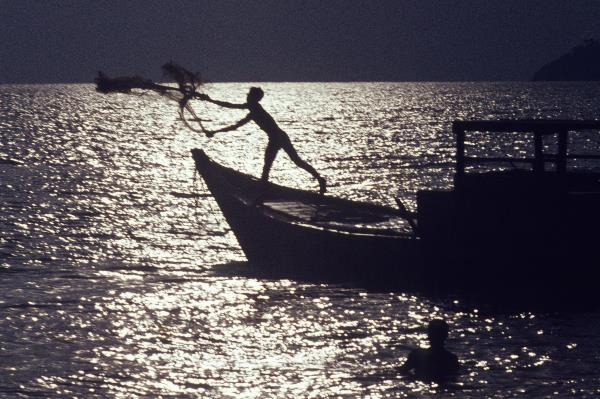 Thailand. Ein Fischer wirft sein Netz aus.