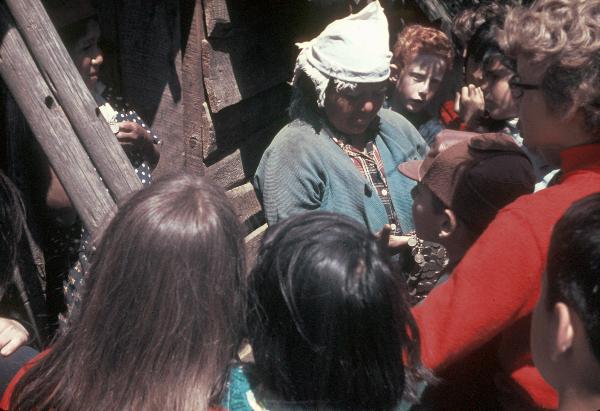 Eine Mapuchenfrau zeigt Schülern typischen Schmuck.